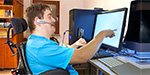 photo of a user with disability operating a computer with headset and touch keyboard