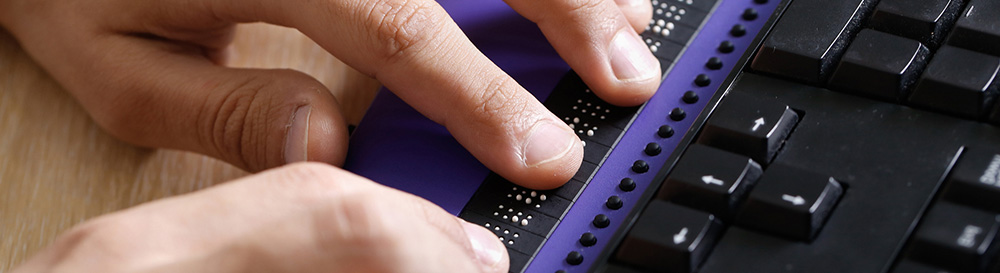 photo of hands operating a computer using a braille keyboard